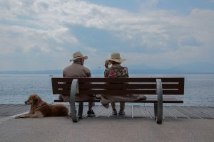 Couple de personnes âgées sur un banc face à la mer en train de promener leur chien