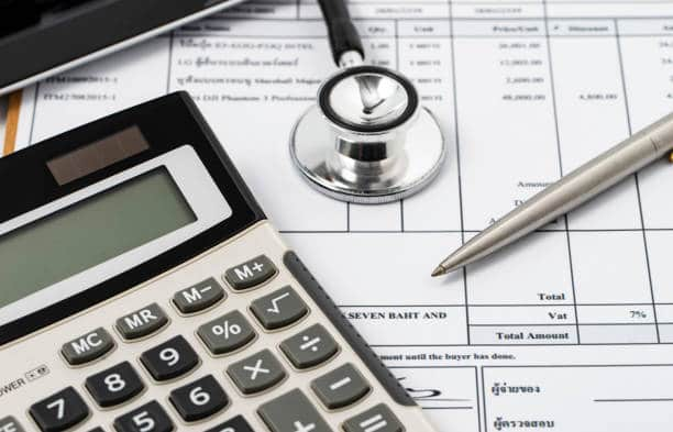 Stéthoscope, calculatrice et stylo sur une facture de médecin