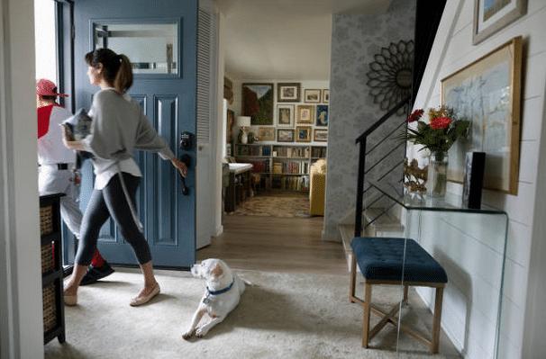 Deux personnes sur le point de sortir de la maison et un chien allongé dans le couloir