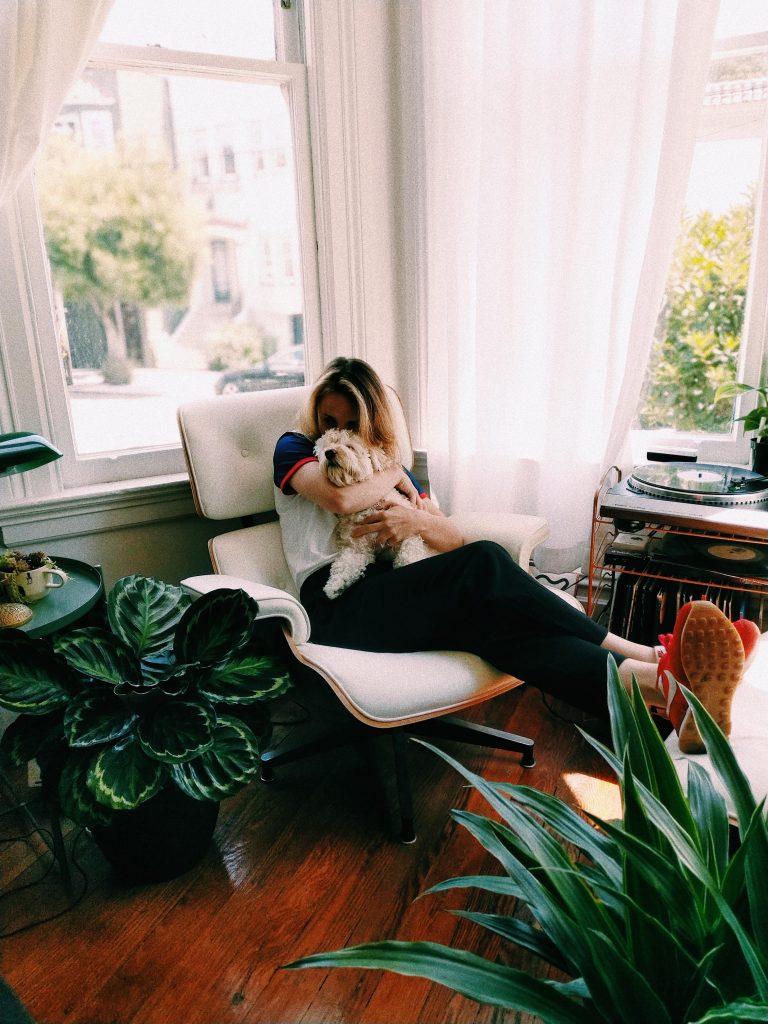 Femme faisant un câlin à son chien sur un fauteuil