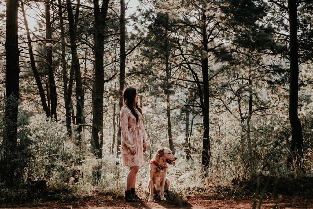 Femme qui promène son chien en forêt